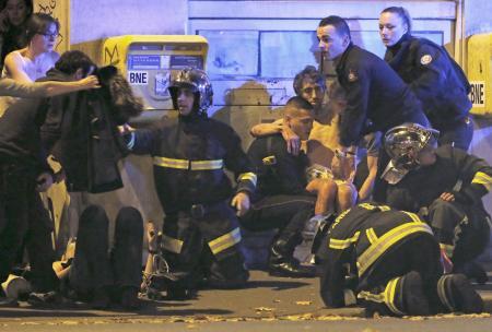 武装集団が銃を乱射するなどしたバタクラン劇場の近くで、負傷者を手当てする救助隊員=13日、パリ(ロイター=共同)