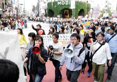 安倍政権への反対を訴えて街を歩く大学生らデモの参加者たち=14日
